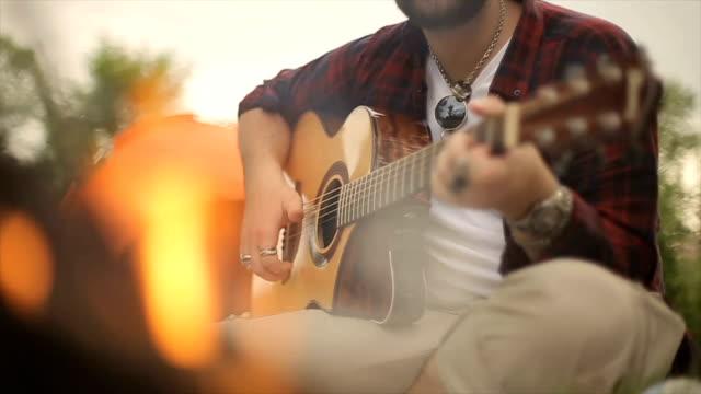 vídeos de stock, filmes e b-roll de um jovem tocando guitarra perto da fogueira - violão acústico