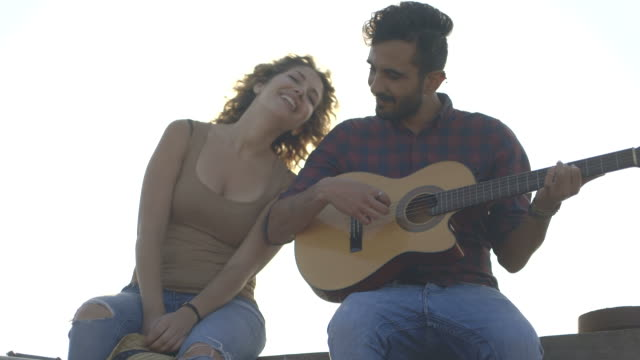 a young man playing guitar with woman - plucking an instrument stock videos and b-roll footage