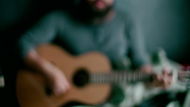 vídeos de stock, filmes e b-roll de homem novo que joga o guiter em casa - dedilhando instrumento