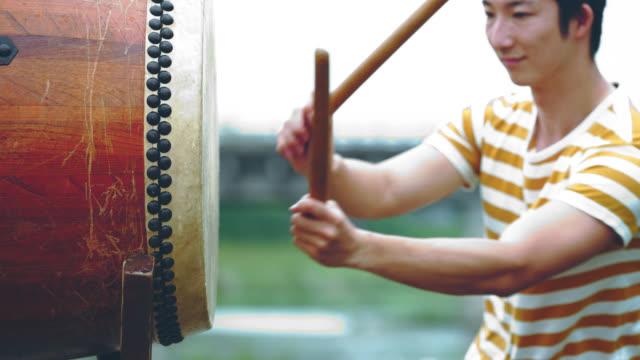 Jonge man spelen Japanse trommel buitenshuis