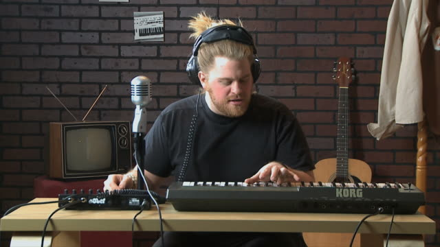 young man playing music on a keyboard in his room - garage stock-videos und b-roll-filmmaterial
