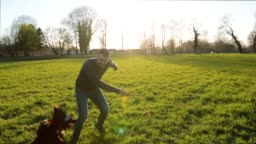 Young man playing outdoors with his dog