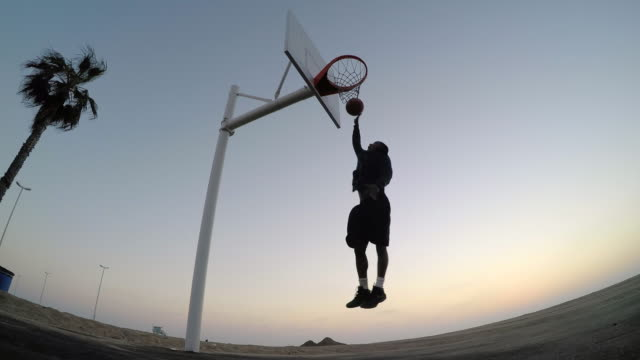 a young man playing street basketball on the beach as the sun sets. - basketball hoop stock videos and b-roll footage