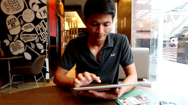 Young man playing tablet in a coffee shop.