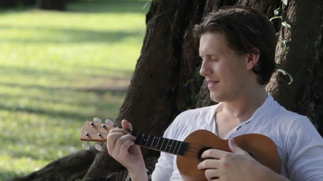 vídeos de stock, filmes e b-roll de cu young man playing ukulele beneath tree / singapore, singapore, singapore - ukulele