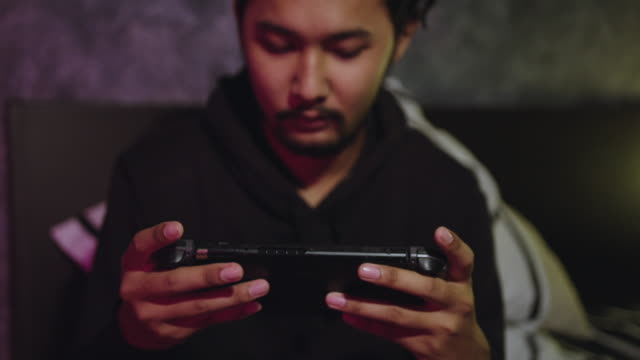 young man playing video game on bedroom - handheld video game stock videos & royalty-free footage