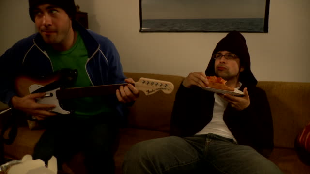 ms young man playing video game with guitar next to man eating pizza sitting on sofa, brooklyn, new york city, new york state, usa - leisure games stock videos & royalty-free footage