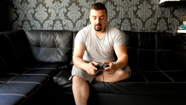 young man playing video games on the couch - gamepad stock videos & royalty-free footage