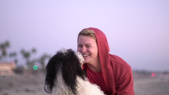 vídeos y material grabado en eventos de stock de cu young man playing with his dog on the beach - enfoque diferencial