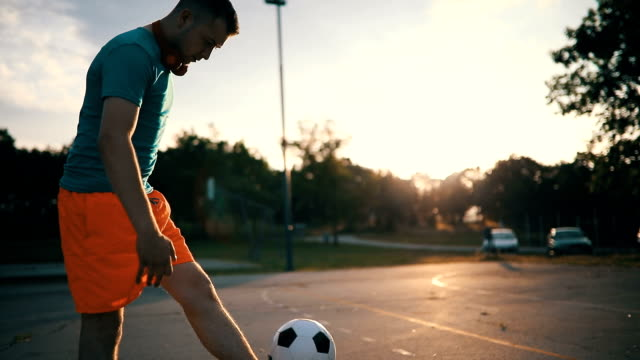 young man playing with soccer ball - juggling stock videos & royalty-free footage