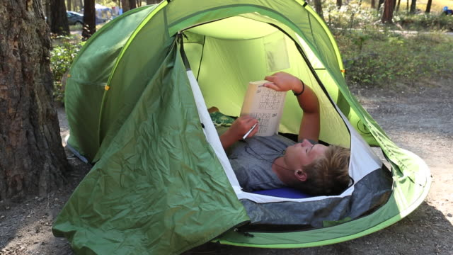 Young man plays book game in tent, at campground