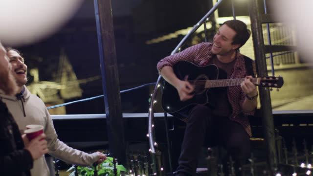 vídeos de stock, filmes e b-roll de ws. young man plays guitar as friends sing along at rooftop party. - violão