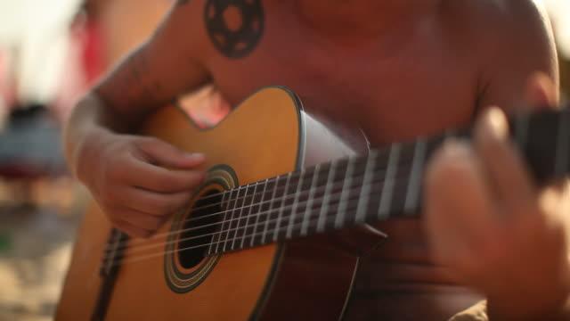 Young man plays guitar on Ipanema Beach at Ipanema Beach on February 01 2012 in Rio de Janeiro Brazil