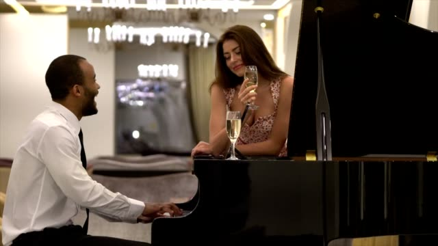 Young man plays piano to his girlfriend