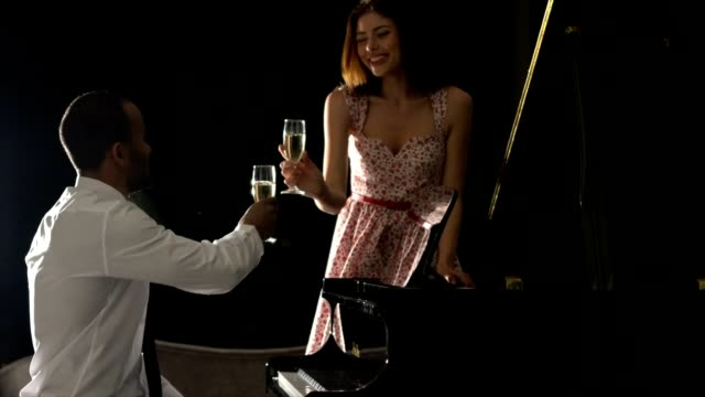 young man plays piano to his girlfriend - bicchiere da vino video stock e b–roll