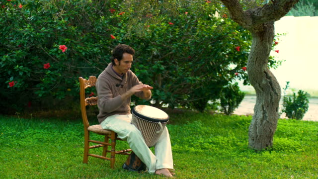 A young man plays the drum in the garden at sunset