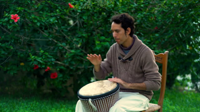 a young man plays the drum in the garden at sunset - silvestre stock-videos und b-roll-filmmaterial