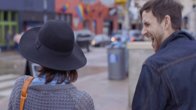 Young man points out destination to girlfriend as they walk through downtown Austin