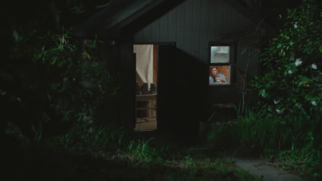 stockvideo's en b-roll-footage met young man polishes part of his project in the shed at night - avondschemering