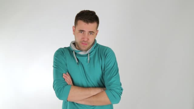 young man posing and looking and winking at camera, arms crossed, studio shot, white background - actor stock videos & royalty-free footage
