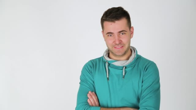 vídeos de stock e filmes b-roll de young man posing and looking at camera, studio shot, white background - só um rapaz