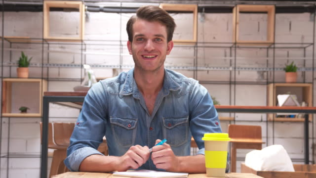 Young man posing in a small office