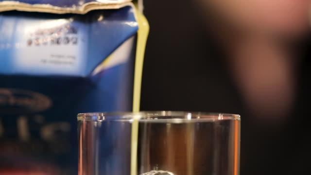 ナイトクラブのバーカウンターでおいしいカクテルのための飲み物グラスにジュースを注ぐ若い男 - オレンジジュース点の映像素材/bロール