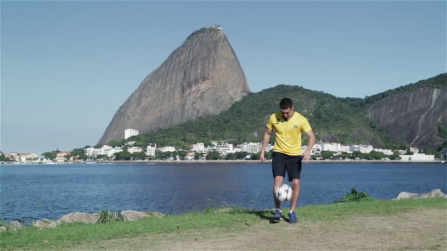 ws a young man practices football skills with sugarloaf mountain or pao de acucar in background / rio de janeiro, brazil - juggling stock videos & royalty-free footage