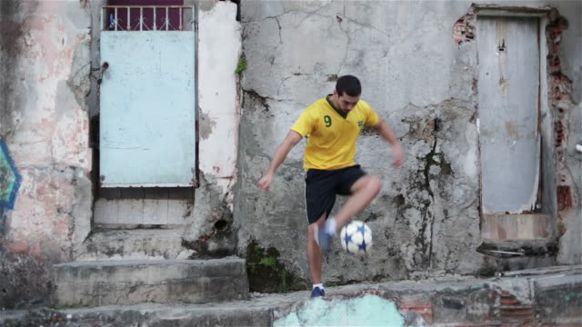 "stockvideo's en b-roll-footage met ""ws a young man practices his football skills in a favela / rio de janeiro, brazil"" - schoppen lichaamsbeweging"