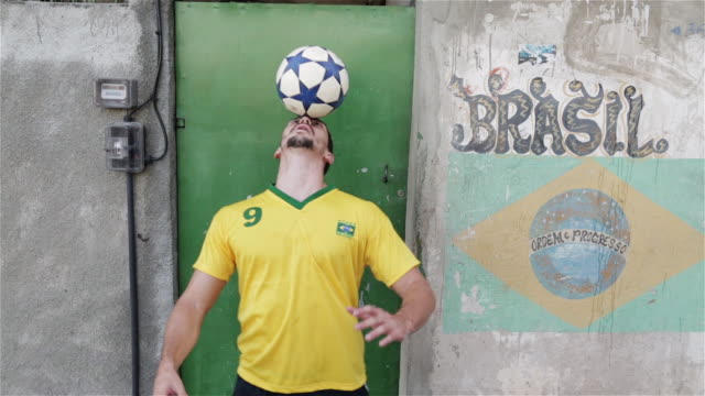 "stockvideo's en b-roll-footage met ""ms a young man practices his football skills in a favela / rio de janeiro, brazil"" - brazilië"
