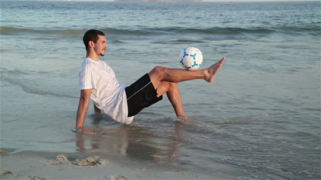 WS A young man practices his football skills on Ipanema beach / Rio de Janeiro, Brazil