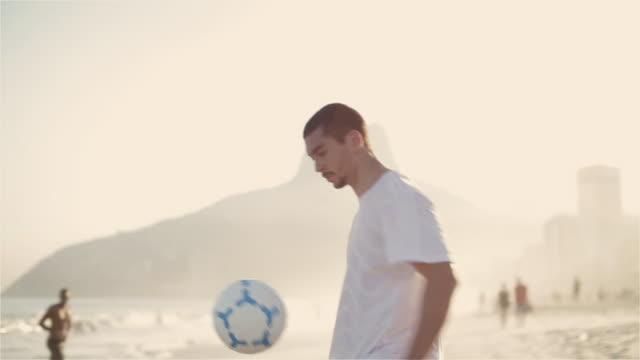 vídeos de stock, filmes e b-roll de ms a young man practices his football skills on ipanema beach / rio de janeiro, brazil - camiseta