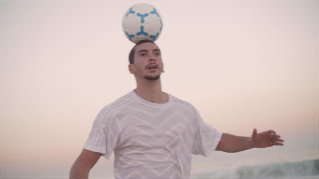 vídeos de stock e filmes b-roll de cu a young man practices his football skills on ipanema beach / rio de janeiro, brazil - saltar para cima e para baixo