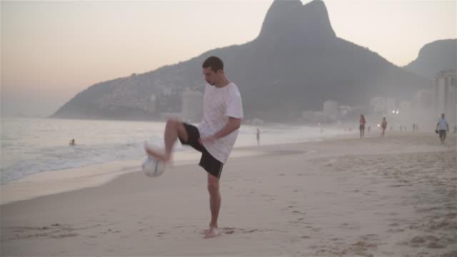 WS A young man practices his football skills on Ipanema beach / Rio de Janeiro, Brazil