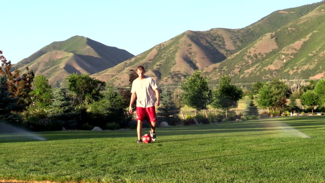 young man practices soccer football skills on lawn