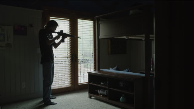 Young man practicing aiming and shooting AR-15 rifle in bedroom / Cedar Hills, Utah, United States