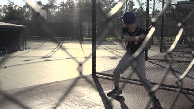 a young man practicing baseball at the batting cages.  - slow motion - gabbia di battuta video stock e b–roll