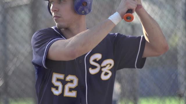 a young man practicing baseball at the batting cages.  - super slow motion - filmed at 240 fps - gabbia di battuta video stock e b–roll