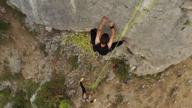 stockvideo's en b-roll-footage met jonge mens die vrij het beklimmen op rots beoefent - free climbing