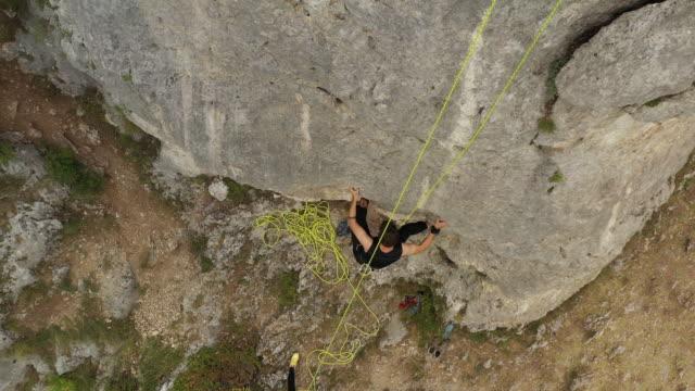 junger mann übt freies klettern auf felsen - free climbing stock-videos und b-roll-filmmaterial
