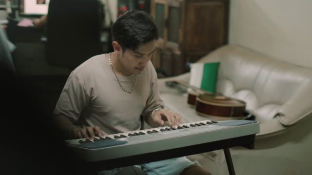 young man practicing piano at home stock video - producer stock videos & royalty-free footage