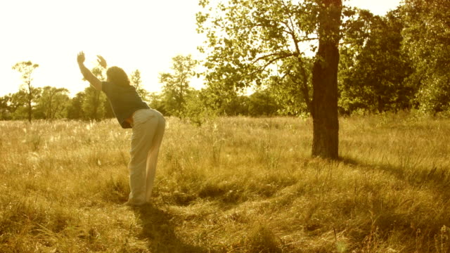 Young man practicing yoga in a summer forest.
