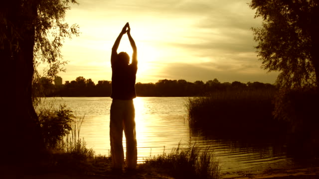 young man practicing yoga near the river - barefoot stock videos & royalty-free footage