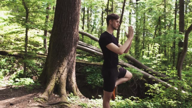 Young man practising yoga in woods