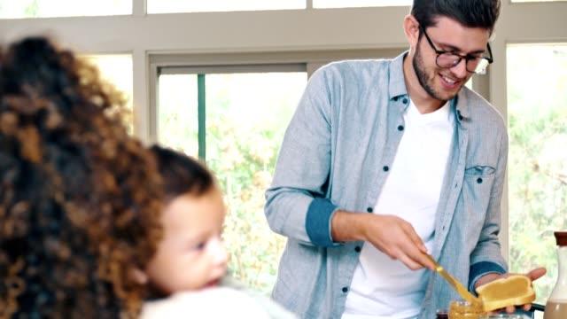 若い男は、彼女が彼らの赤ちゃんの世話をしながら、彼の妻のために昼食を準備します - サンドイッチ作り点の映像素材/bロール