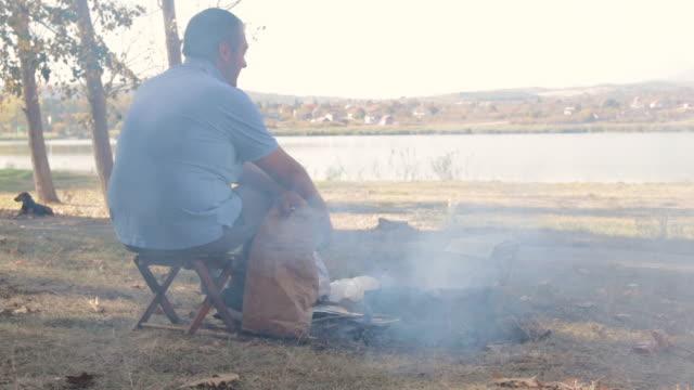 junger mann bereitet grill in der natur mit seinen hunden - picknick stock-videos und b-roll-filmmaterial