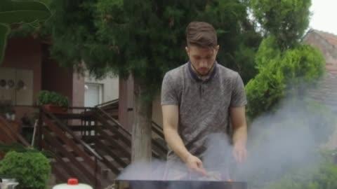 vídeos y material grabado en eventos de stock de hombre joven preparando barbacoa - asado alimento cocinado