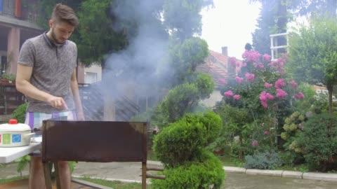 vídeos y material grabado en eventos de stock de hombre joven preparando barbacoa - cocido a la parrilla