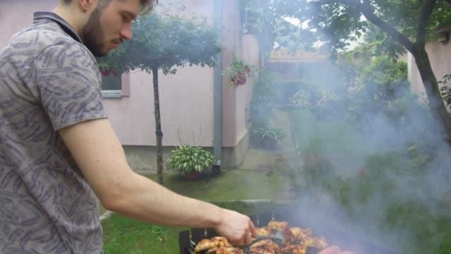 vídeos y material grabado en eventos de stock de hombre joven preparando barbacoa - formal garden