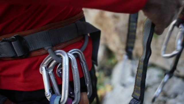 a young man preparing carabiners to go rock climbing. - climbing equipment stock videos and b-roll footage